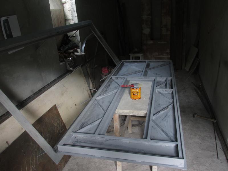 Металлическая дверь сокном идекором втехнике холодной ковки